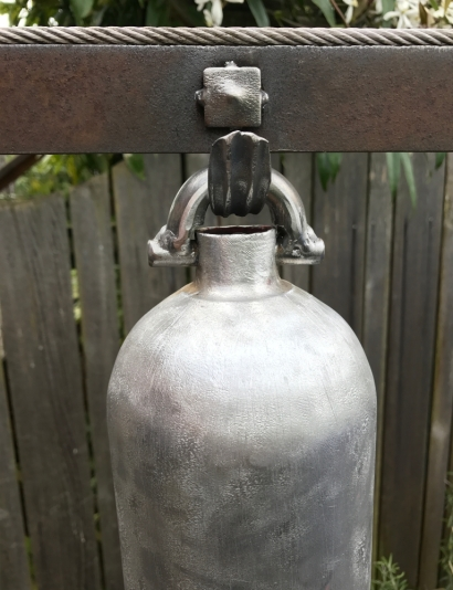 """aluminum bell with stainless steel accent : Created from fire extinguisher, laser cut drop, chain, square washer, vintage twist drill wood handle, stainless steel cable, plow disc and plumbing from my bathroom remodel. - 24"""" W x 64"""" H"""