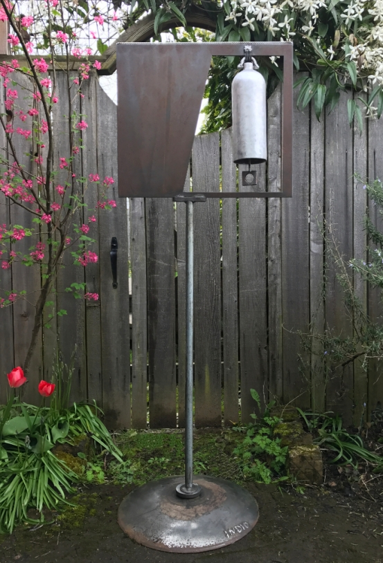"""Aluminum Bell with Stainless Steel Accent- 24"""" W x 64"""" H. Created from fire extinguisher, laser cut drop, chain, square washer, vintage twist drill wood handle, stainless steel cable, plow disc and plumbing from my bathroom remodel."""