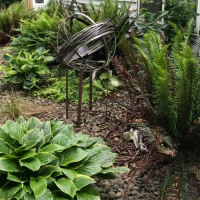 This Stainless Whirling Orb is set in a side yard rock garden.